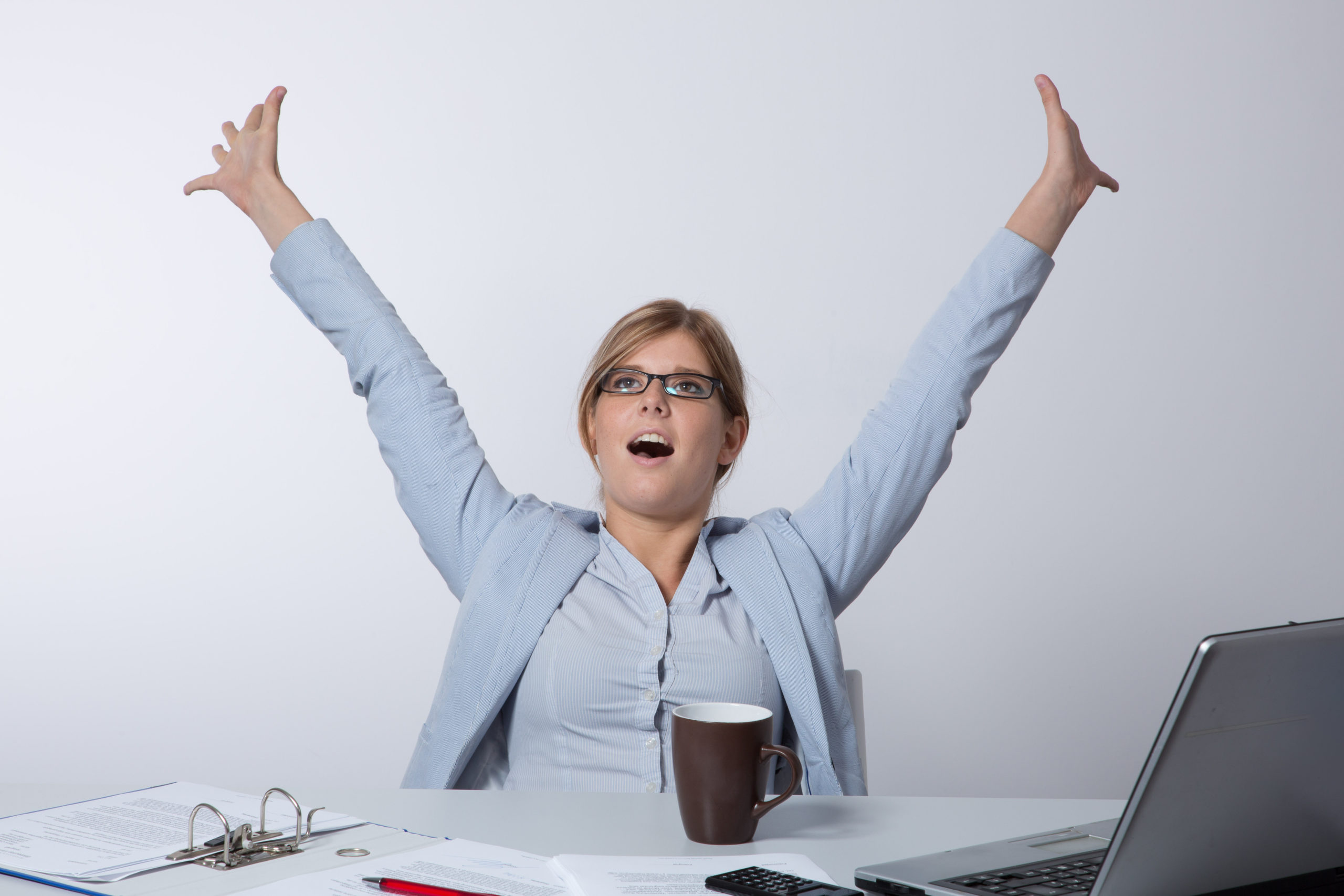 Junge Frau freut sich am Schreibtisch