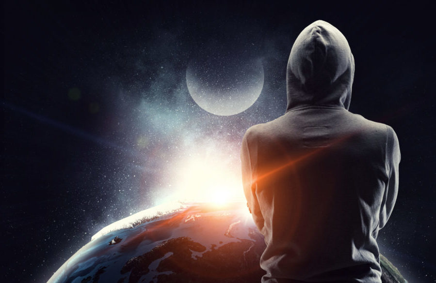 Almost unrecognizable man wearing hood on dark background. Elements of this image are furnished by NASA